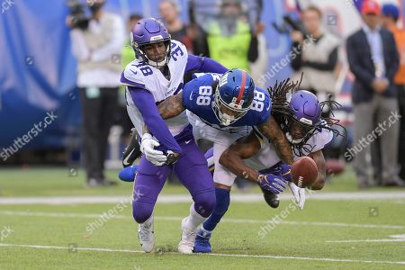 Minnesota Vikings defensive back Kris Boyd (38) and defensive back Anthony Harris (41) break up a pass intended for New York Giants tight end Evan Engram (88) during the fourth quarter of an NFL football game, in East Rutherford, N.J