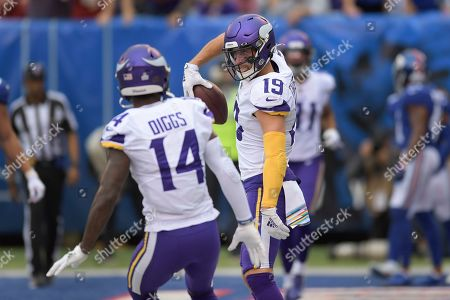 Minnesota Vikings wide receiver Adam Thielen (19) celebrates with wide receiver Stefon Diggs (14) after scoring a touchdown against the New York Giants during the second quarter of an NFL football game, in East Rutherford, N.J