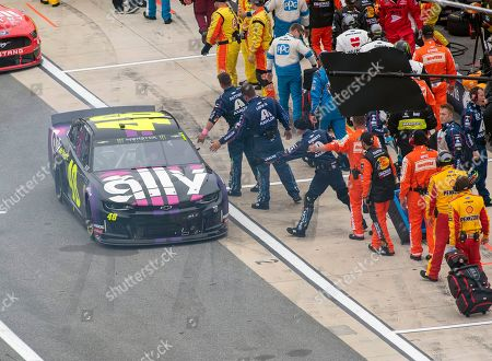 Jimmie Johnson's team puts out their hands as he leaves pit road for the start of the Drydene 400 - Monster Energy NASCAR Cup Series playoff auto race, at Dover International Speedway in Dover, Del