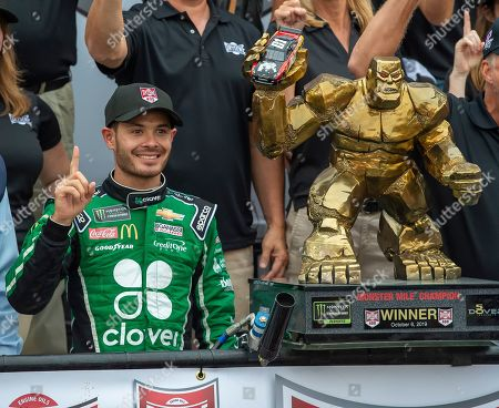 Kyle Larson stands next to the trophy after winning the NASCAR Cup Series auto race, at Dover International Speedway in Dover, Del