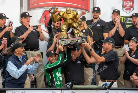 Kyle Larson, front left center, gets help in holding up the trophy after his win in the NASCAR Cup Series auto race, at Dover International Speedway in Dover, Del
