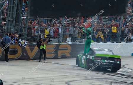 Kyle Larson stands on his car and waves to crowd after winning the NASCAR Cup Series playoff auto race, at Dover International Speedway in Dover, Del