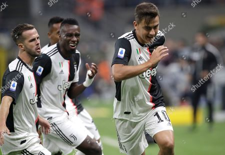 Juventus' Paulo Dybala, right, celebrates with teammates after scoring the opening goal during a Serie A soccer match between Inter Milan and Juventus, at the San Siro stadium in Milan, Italy