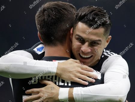 Juventus' Paulo Dybala, left, celebrates with teammate Juventus' Cristiano Ronaldo after scoring the opening goal during a Serie A soccer match between Inter Milan and Juventus, at the San Siro stadium in Milan, Italy