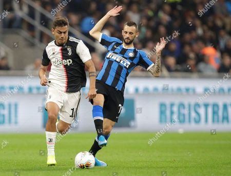 Juventus' Paulo Dybala, left, fights for the ball with Inter Milan's Marcelo Brozovic during a Serie A soccer match between Inter Milan and Juventus, at the San Siro stadium in Milan, Italy