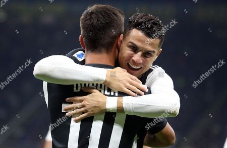 Juventus' Paulo Dybala  celebrates with his teammate Cristiano Ronaldo (R) after scoring the 0-1 goal during the Italian serie A soccer match between FC Inter and Juventus FC at Giuseppe Meazza stadium in Milan, Italy, 6 October 2019.