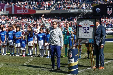 Stock Image of United States head coach Jill Ellis waves to the crowd as she is honored during a ceremony before an international friendly soccer match against South Korea, in Chicago