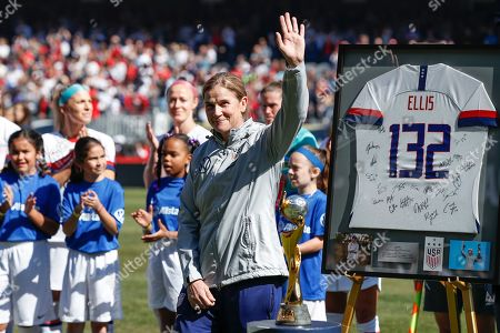Stock Photo of United States head coach Jill Ellis waves to the crowd as she is honored during a ceremony before an international friendly soccer match against South Korea, in Chicago