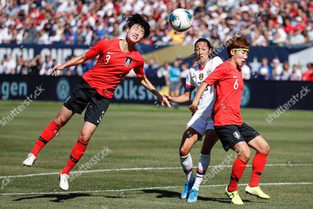 South Korea defenders Hong Hyeji, left, and Lim Seonjoo, right, defend against United States forward Christen Press, center, during the first half of an international friendly soccer match, in Chicago