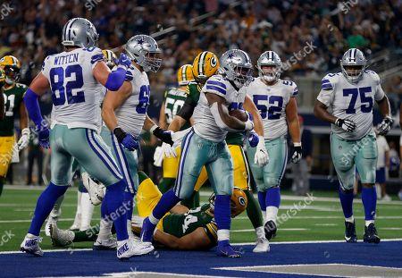 Ezekiel Elliott, Jason Witten, Connor Williams, Cameron Fleming. Dallas Cowboys' Ezekiel Elliott (21) celebrate his touchdown run as Jason Witten (82), Connor Williams (52), Cameron Fleming (75) and others look on in the second half of an NFL football game in Arlington, Texas