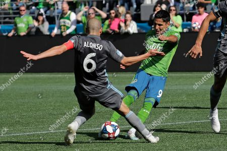 Seattle Sounders forward Raul Ruidiaz, right, has a shot on goal blocked by Minnesota United midfielder Osvaldo Alonso (6), during the first half of an MLS soccer match, in Seattle