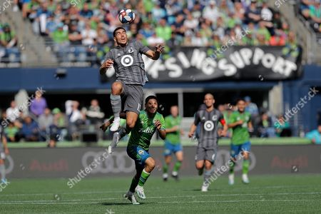 Minnesota United defender Michael Boxall, left, heads the ball above Seattle Sounders forward Raul Ruidiaz, second from left, during the first half of an MLS soccer match, in Seattle