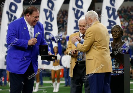 Pro Football Hall of Fame President C. David Baker, left, and Dallas Cowboys owner Jerry Jones, right, present Gil Brandt, center, with his Hall of Fame ring during a ceremony at halftime of the Cowboys' NFL football game against the Green Bay Packers in Arlington, Texas