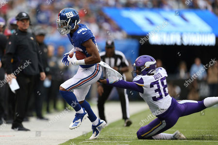 New York Giants tight end Evan Engram (88) completes pass as Minnesota Vikings defensive back Kris Boyd (38) tries to tackle him during an NFL football game, in East Rutherford, N.J. The Giants lost 28-10