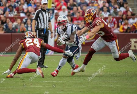 New England Patriots running back James White (28) carries the ball in the fourth quarter against the Washington Redskins. Defending on the play are Washington Redskins cornerback Josh Norman (24) and linebacker Cole Holcomb (55). The Patriots won the game 33 - 7.