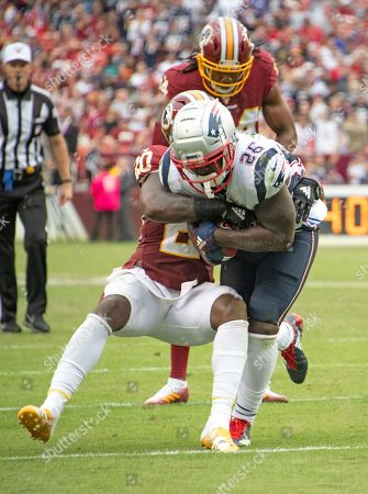 New England Patriots running back Sony Michel (26) is tackled by Washington Redskins strong safety Landon Collins (20) and cornerback Josh Norman (24) in the fourth quarter of the game. The Patriots won the game 33 - 7.