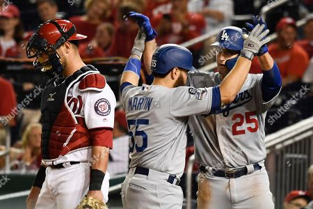 Los Angeles Dodgers' Russell Martin (55) celebrates with David Freese (25) after hitting a two-run home run off Washington Nationals relief pitcher Hunter Strickland during the ninth inning in Game 3 of a baseball National League Division Series, in Washington. At left is Nationals catcher Kurt Suzuki