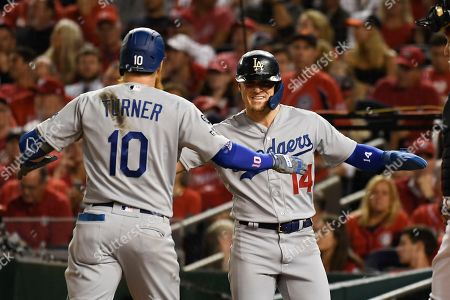 Los Angeles Dodgers' Justin Turner (10) celebrates his three-run home run off Washington Nationals relief pitcher Wander Suero with Enrique Hernandez (14) during the sixth inning in Game 3 of a baseball National League Division Series, in Washington