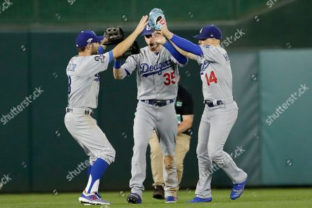 Los Angeles Dodgers Chris Taylor, left, Cody Bellinger (35) and Enrique Hernandez (14) celebrate the team's 10-4 win over the Washington Nationals in Game 3 of a baseball National League Division Series, in Washington