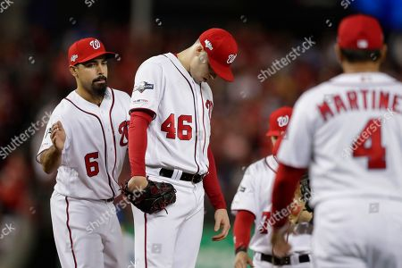 Washington Nationals pitcher Patrick Corbin, lowers his head as manager Dave Martinez, right, walks over during a pitching change in the sixth inning against the Los Angeles Dodgers during Game 3 of a baseball National League Division Series, in Washington. Patting Corbin on the back Anthony Rendon (6). Corbin was charged with six of the Dodgers' seven runs in the inning. The Dodgers won 10-4