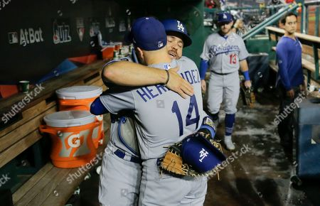 Los Angeles Dodgers catcher Russell Martin (55) and second baseman Enrique Hernandez (14) embrace in the dugout after Game 3 of the baseball team's National League Division Series against Washington Nationals, in Washington. The Dodgers won 10-4