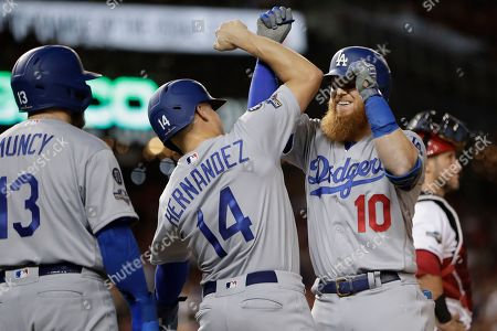 Los Angeles Dodgers third baseman Justin Turner (10) celebrates his three-run home run off Washington Nationals relief pitcher Wander Suero with teammates Enrique Hernandez (14) and Max Muncy (13) during the sixth inning in Game 3 of a baseball National League Division Series, in Washington
