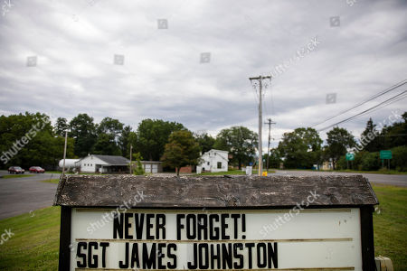 A sign remembering Sgt. James Johnston, who was killed in Afghanistan in June, stands outside the American Legion hall in Trumansburg, N.Y., . As the nation's longest war marks the end of its 18th year, James' widow, Krista Johnston, returned to her tiny hometown for two milestones: In one weekend at the hall, she joined hundreds to pay tribute to her husband with a 21-gun salute, TAPS and remembrances. A day later, she returned for a baby shower, celebrating the impending birth of their daughter he didn't live to see. The little girl will be named for her father