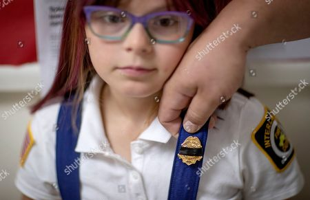 Dani Nelson, 7, wears a junior fire badge covered in black tape, a gesture of mourning, by her father, Chris Nelson, a member of the Enfield Volunteer Fire Company where Sgt. James Johnston once served, before a memorial procession for him in Enfield, N.Y., . Johnston, an explosive ordnance disposal specialist, had been killed along with a Green Beret on June 25 in Uruzgan Province in south-central Afghanistan