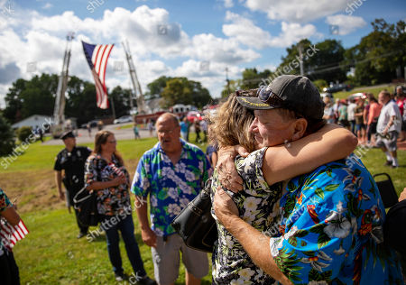 Fred VanDerzee, right, is embraced by Sarah Short at a memorial service, in Trumansburg, N.Y., for his son-in-law, Sgt. James Johnston, who was killed in Afghanistan in June