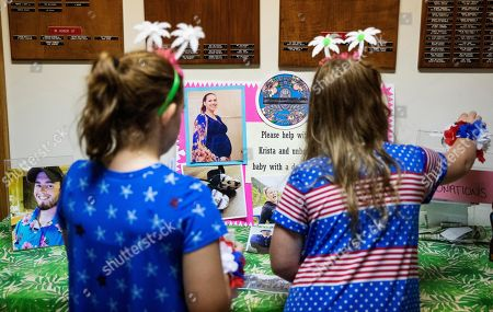 Haileigh, 8, right, and sister, Brooke, 10, Hitchcock, place a donation for Sgt. James Johnston, an Army soldier killed in Afghanistan in June, and his pregnant wife, Krista, during a memorial in Trumansburg, N.Y., . As the nation's longest war marks the end of its 18th year, Krista returns to her tiny hometown for two milestones: In one weekend in the local American Legion hall, she joins hundreds to pay tribute to her husband with a 21-gun salute, TAPS and remembrances. A day later, she returns for a baby shower, celebrating the impending birth of their daughter he didn't live to see