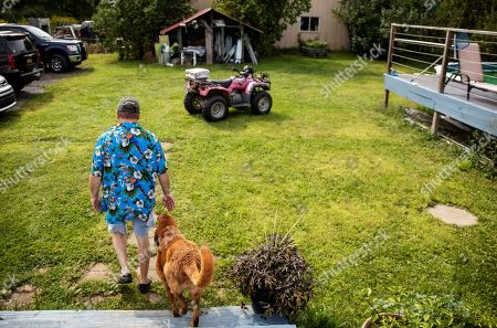 """Fred VanDerzee and his dog Copper, walk outside their home, where Vanderzee's son-in-law, Sgt. James Johnston, who was killed in Afghanistan in June, once lived in Trumansburg, N.Y., . VanDerzee was so fond of him he called him the """"son I never had"""