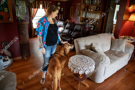 """Krista Johnson and her dog Copper stand in her childhood home in Trumansburg, N.Y., where she once lived with her husband, Sgt. James Johnston, who was killed in Afghanistan in June. On June 25th, Krista and James did what they'd done since he arrived in Afghanistan. He messaged her that he'd be going on an operation. """"Be safe. I love you,"""" she'd responded, and she awaited word that he had returned safely. This time, there was silence"""