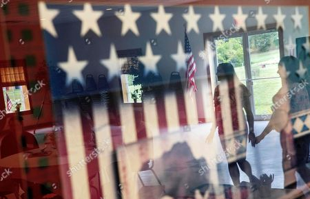 Krista Johnston, left, and her friend Courtney Nichols, are reflected in American flag artwork hanging in the American Legion during a joint baby shower for the two friends in Trumansburg, . Johnston's husband, Sgt. James Johnston, was killed in Afghanistan in June just months after learning he would become a father