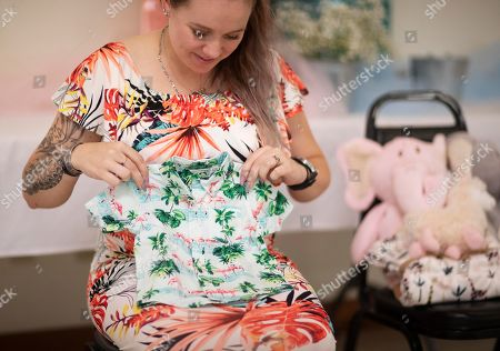 Krista Johnston looks at a tiny Hawaiian shirt given as a gift during a baby shower at the American Legion in Trumansburg, N.Y., . Johnston's husband, Sgt. James Johnston, who loved Hawaiian shirts, was killed in Afghanistan in June just months after learning he would become a father