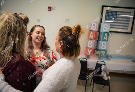 Krista Johnston, center, is embraced at her baby shower at the American Legion hall by friend Ashley Percey, right, and Percey's mother Lisa Park, in Trumansburg, N.Y., . Johnston's husband, Sgt. James Johnston, was killed in Afghanistan in June just months after learning he would become a father