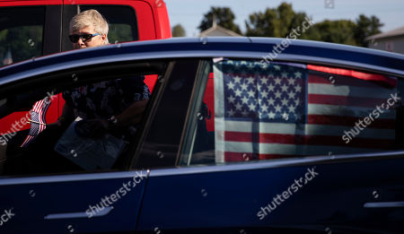 County legislator Anne Koreman decorates her car with American flags before a memorial procession in Enfield, N.Y., for Sgt. James Johnston, who was killed in Afghanistan in June