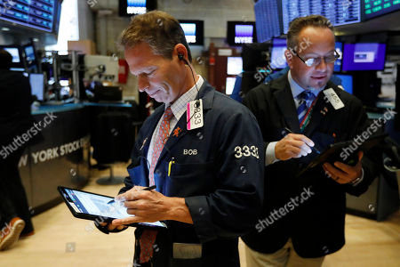Trader Robert Charmak, left, works on the floor of the New York Stock Exchange, . Stocks are opening broadly lower on Wall Street, extending the market's losing streak into a fourth week