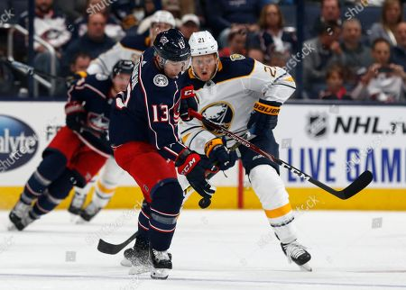 Columbus Blue Jackets forward Cam Atkinson, left, controls the puck against Buffalo Sabres forward Kyle Okposo during the first period of an NHL hockey game in Columbus, Ohio