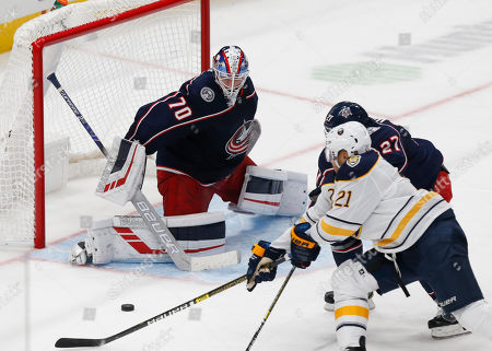 Stock Photo of Columbus Blue Jackets goalie Joonas Korpisalo, left, of Finland, stops a shot by Buffalo Sabres forward Kyle Okposo, right, as Blue Jackets defenseman Ryan Murray defends during the third period of an NHL hockey game in Columbus, Ohio
