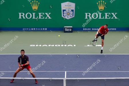 Novak Djokovic, Filip Krajinovic. Filip Krajinovic of Serbia hits a serve not ti his compatriot Novak Djokovic as they play against Kevin Krawietz and Andreas Mies of Germany during the men's doubles match at the Shanghai Masters tennis tournament at Qizhong Forest Sports City Tennis Center in Shanghai, China