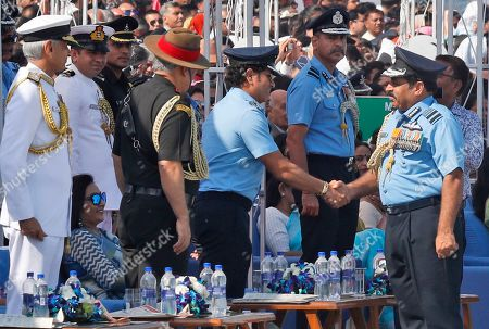 Former Indian cricketer and honorary Indian Air Force (IAF) officer Sachin Tendulkar, cente right, shakes hand with Indian Air Force chief Air Chief Marshal Rakesh Kumar Bhadauria during Air Force Day parade at the Hindon air base on the outskirts of New Delhi, India . Air Force Day is celebrated to mark the day the Indian air force, the fourth largest air force in the world, was officially established in 1932. Apart from defending Indian air space, the air force also delivers humanitarian aid and disaster relief material during natural calamities