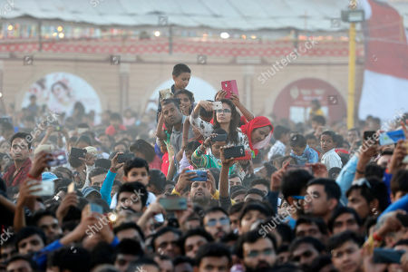 People take pictures on their mobile phones at an event marking the end of Dussehra festival in New Delhi, India, Tuesday, Oct.8, 2019. Dussehra commemorates the triumph of Lord Rama over the demon king Ravana, marking the victory of good over evil
