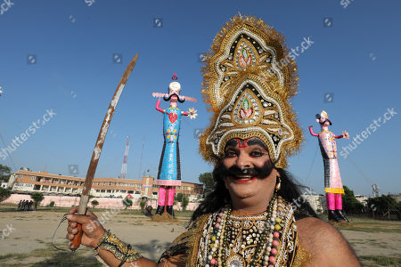 An Indian artist dressed as a demon performs in front of an effigy of demon king Ravana and Kumbhkarana during Dussehra festival celebrations in Jammu, the winter capital of Kashmir, India, 08 October 2019. Dussehra is an annual Hindu religious festival which follows the nine-day festival of Navratri and is celebrated as the victory of the mythological Hindu God Lord Rama over the evil demon king Ravana.