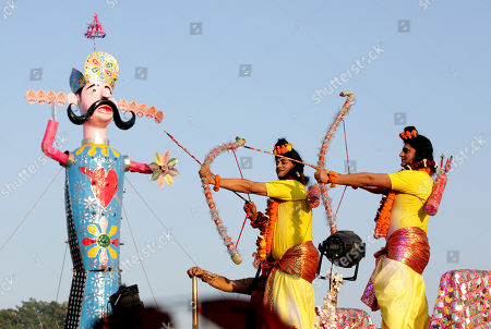 Indian artists dressed as Hindu God Lord Rama (R) and his younger brother Lakshman (L) hold bows and arrows in front of an effigy of demon king Ravana during Dussehra festival celebrations in Jammu, the winter capital of Kashmir, India, 08 October 2019. Dussehra is an annual Hindu religious festival which follows the nine-day festival of Navratri and is celebrated as the victory of the mythological Hindu God Lord Rama over the evil demon king Ravana.