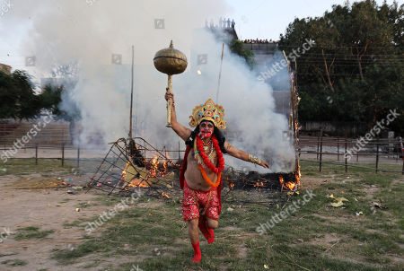 An Indian devotee dressed as Hindu monkey god Hanuman shout slogans after an effigy of demon king Ravana's kingdom of Lanka is set ablaze during the Dussehra festival celebrations in Jammu, the winter capital of Kashmir, India, 08 October 2019. Dussehra is an annual Hindu religious festival which follows the nine-day festival of Navratri and is celebrated as the victory of the mythological Hindu God Lord Rama over the evil demon king Ravana.