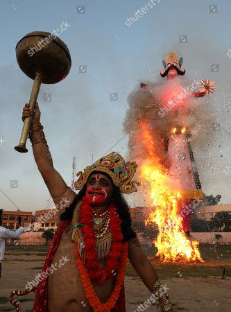 An Indian devotee dressed as Hindu monkey god Hanuman celebrates after an effigy of demon king Ravana's kingdom of Lanka is set ablaze during the Dussehra festival celebrations in Jammu, the winter capital of Kashmir, India, 08 October 2019. Dussehra is an annual Hindu religious festival which follows the nine-day festival of Navratri and is celebrated as the victory of the mythological Hindu God Lord Rama over the evil demon king Ravana.