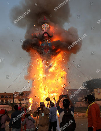 People watch the burning effigy of demon king Ravana during the Dussehra festival celebrations in Jammu, the winter capital of Kashmir, India, 08 October 2019.Dussehra is an annual Hindu religious festival which follows the nine-day festival of Navratri and is celebrated as the victory of the mythological Hindu God Lord Rama over the evil demon king Ravana.