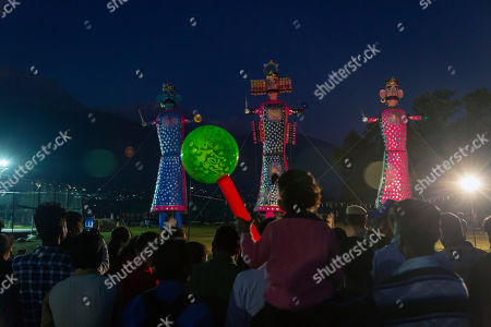 People wait for effigies of mythological demon king Ravana, center, his brother and his son to burn marking the end of Dussehra festival in Dharmsala, India, . Dussehra commemorates the triumph of Lord Rama over the demon king Ravana, marking the victory of good over evil