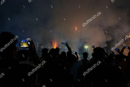 People take cellphone photos of a fireworks display after effigies of mythological demon king Ravana, his brother and his son, are burnt marking the end of Dussehra festival in Dharmsala, India, . Dussehra commemorates the triumph of Lord Rama over the demon king Ravana, marking the victory of good over evil