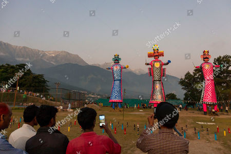 People take cellphone photos of effigies of mythological demon king Ravana, center, his brother and his son marking the end of Dussehra festival in Dharmsala, India, . Dussehra commemorates the triumph of Lord Rama over the demon king Ravana, marking the victory of good over evil
